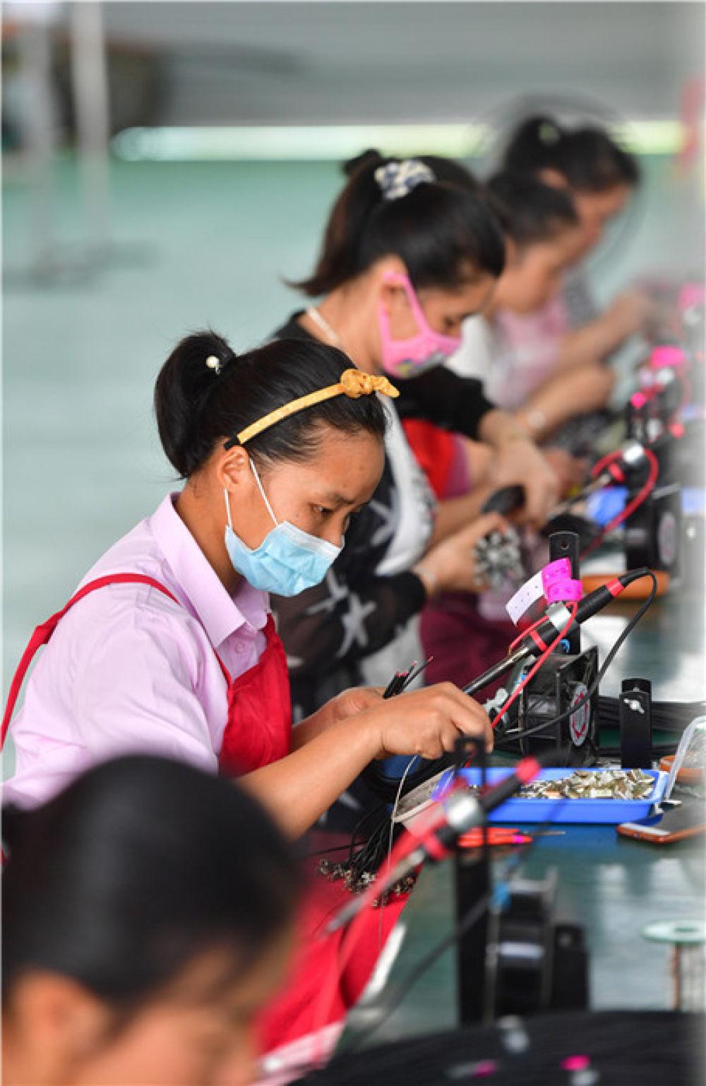 5月17日,在广西融安县农产品加工暨粤桂扶贫协作产业园,一家电子产品企业的工人在扶贫车间生产线上作业。新华社记者 黄孝邦 摄
