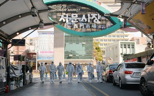 23日在韩国大邱,受疫情影响而临时休业的商家工作人员在西门市场进行防疫消毒。