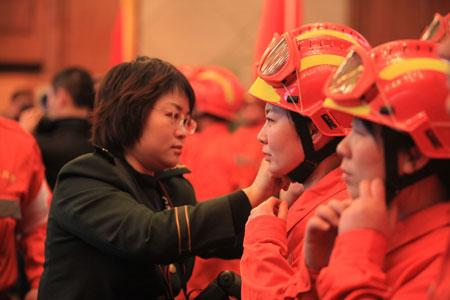A female armed police official helps fastening helmet of a female member of a Chinese rescue team before the 50-member team's departure for quake-hit Haiti, at the Capital International Airport in Beijing, capital of China, Jan. 13, 2010. The team consist of search and rescue personnel, who have conducted many rescue tasks of this kind in the past years, and three sniffer dogs.(Xinhua/Xing Guangli)