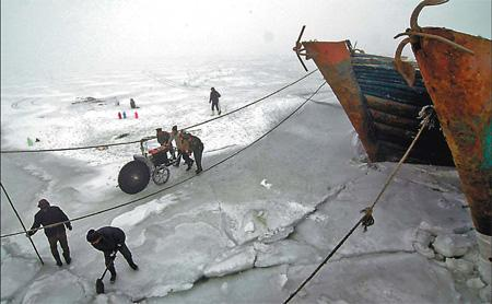 Fishermen in Jinzhou, Northeast China's Liaoning province, try to break the ice in the Bohai Sea on Monday. [Li Tiecheng/China Daily]