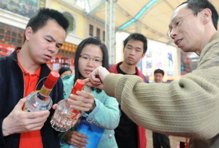 ConsumerslearntodistinguishgenuineliquorfromthefakeversionduringaconsultationactivityheldfortheannualWorldConsumerRightsDayinFoshan,SouthChina'sGuangdongprovince.[Photo/CFP]