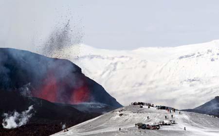 TouristsgathertowatchlavaspurtoutofthesiteofavolcaniceruptionattheFimmvorduhalsvolcanoneartheEyjafjallajokullglacier,some125kmseastofReykjakiconMarch27.(Xinhua/AFP,FilePhoto)