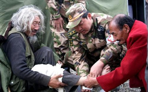 A medical worker of the Chinese public security frontier defense troop helps Zhaxi Deleg of the Tibetan ethnic group injured in the earthquake to bandage up his leg in Gyegu Town of Yushu County, northwest China's Qinghai Province, April 20, 2010.  (Xinhua/Wang Xiaoxue)