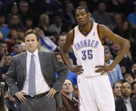 Oklahoma City Thunder head coach Scott Brooks (L) and guard Kevin Durant (35) watch from the bench as a San Antonio Spurs player shoots free throws in the first half during their NBA basketball game in Oklahoma City, Oklahoma, March 22, 2010.[Photo/Agencies]