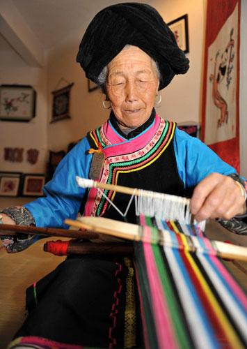 A 71-year-old embroiderer of Qiang ethnic group weaves a waistband on her loom in Jina village in Beichuan County, Southwest China's Sichuan province, May 13, 2010. To keep the Qiang ethnic group's intangible culture alive after the 8.0-magnitude earthquake two years ago, the villagers set up embroidery training classes and made sure they passed their handiwork skills down the family line. Like other Qiang women, the woman was taught embroidery by her mother and since the age of four or five she has practiced it, decorating every piece of her family's cloth house wares. [Photo/Xinhua]