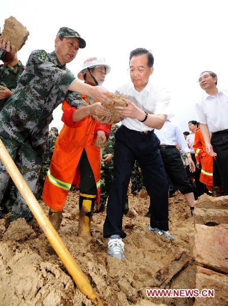 Chinese Premier Wen Jiabao (front R) cleans ruins with rescuers in Shuangshang village in Cangwu County of southwest China's Guangxi Zhuang Autonomous Region, June 20, 2010. Wen Jiabao inspected flood-affected area in Guangxi from June 19 to 20.(Xinhua/Li Tao)