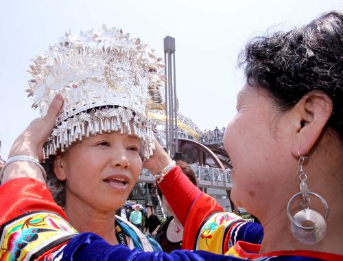 A woman of the Miao nationality puts a traditional headpiece on Tomiyo Yamada at the Expo Park May 1.[Xinhua]