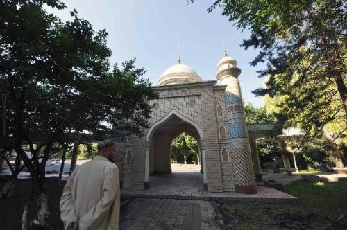 A working staff walks at the Xinjiang Islamic Scripture College in Urumqi, capital of northwest China's Xinjiang Uygur Autonomous Region, June 26, 2010. High school graduated students aged 18 to 25 across Xinjiang will be enrolled in the college, giving lectures in both Ugyur language and Arabic. About 70 percent of the classes given are religious ones. Every students in the government-funded college will get a monthly dining subsidy of 120 RMB. Graduates of the college will receive a religious bachelor's degree and serve in mosques and Islamic associations across the region.(Xinhua/Zhao Ge)