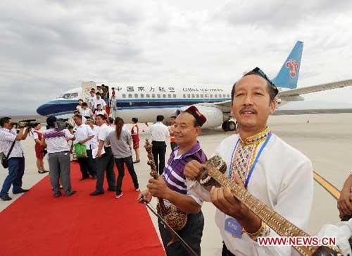 Passengers walk down stairs from the first plane that lands in Turpan airport in northwest China's Xinjiang Uygur Autonomous Region, July 9, 2010. Turpan airport opened to air traffic Friday as a plane of China's Hainan Airlines landed here. (Xinhua/Zhao Ge)