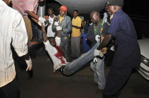 Peoplecarryaman,injuredinanexplosion,uponhisarrivalattheMulagoHospitalinKampalaJuly12,2010.(Xinhua/ReutersPhoto)