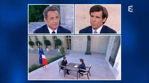 France's President Sarkozy (L), seen in this video grab from France2 Television, appears during a prime time news interview with journalist David Pujadas on France2 television in the garden of the Elysee Palace in Paris July 12, 2010.(Xinhua/AFP Photo)