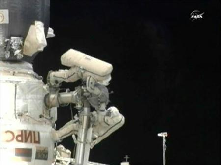 Russian spacewalkers Fyodor Yurchikhin and Mikhail Kornienko, who have identical markings on their spacesuits, get into position to jettison a video camera from the International Space Station in this image from NASA TV July 27, 2010. The spacewalkers will work to outfit the Russian Rassvet module's Kurs automated rendezvous system, install cables, and remove and replace a video camera during their extravehicular excursion.(Xinhua/Reuters Photo)