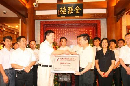 Deputy diretor of the Beijing Tourism Bureau Sun Weijia hands over Beijing Tourist Information board to general manager assistant of China Beijing Quanjude Group on Wednesday, August 4th, 2010. [Photo: CRIENGLISH.com]