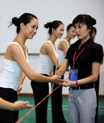 An instructor (R) corrects the gesture of a hostess candidate at the Southern Medical University's Shunde campus in Shunde, Guangdong province, August 5. After 40 days of training, 380 out of 550 candidates will be selected as volunteer hostesses of the 16th Asian Games, which will be held in the provincial capital of Guangzhou from November 12 to 27, 2010.(Photo/Xinhua)