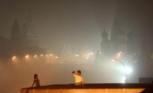 A couple visit the Red Square among thick smog in Moscow, capital of Russia, Aug. 4, 2010. Moscow suffered serious air pollution due to the forest and peat fires. (Xinhua/Lu Jinbo)