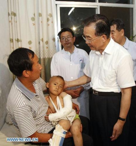 Chinese Premier Wen Jiabao(R front) visits injured persons who got hurt during the landslides at a hospital in Zhouqu County, Gannan Tibetan Autonomous Prefecture in northwest China's Gansu Province, Aug. 8, 2010. (Xinhua/Li Xueren)