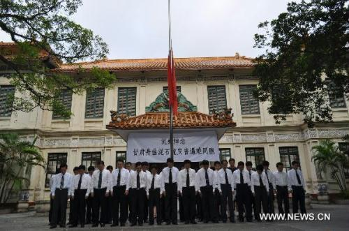 The national flag of China is seen at half mast as Chinese people pay a silent tribute to the victims of the Aug. 8 mudslide disaster in Zhouqu County, Gannan Tibetan Autonomous Prefecture in northwest China's Gansu Province, at the Chinese Embassy in Hanoi, capital of Vietnam, Aug. 15, 2010. China on Sunday held mounrings for the mudslide victims, all over the country and at overseas embassies and consulates. (Xinhua/Li Qing)