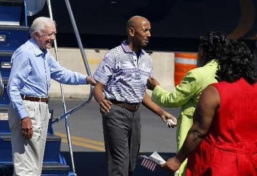 Aijalon Gomes is directed to his family by former President Jimmy Carter at Logan International Airport in Boston, Aug. 27, 2010.(Xinhua/Reuters Photo)
