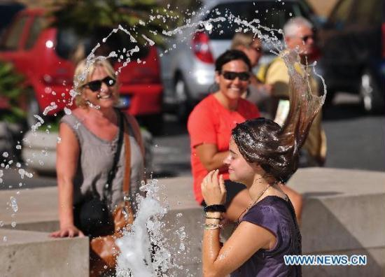 A girl cools off in a fountain in downtown Rome, capital of Italy, July 12, ...