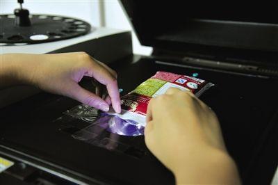 实验人员再用台式X荧光能谱仪对包装检测,两次测试结果均为不含重金属铅、铬、汞。实习生黄怡摄