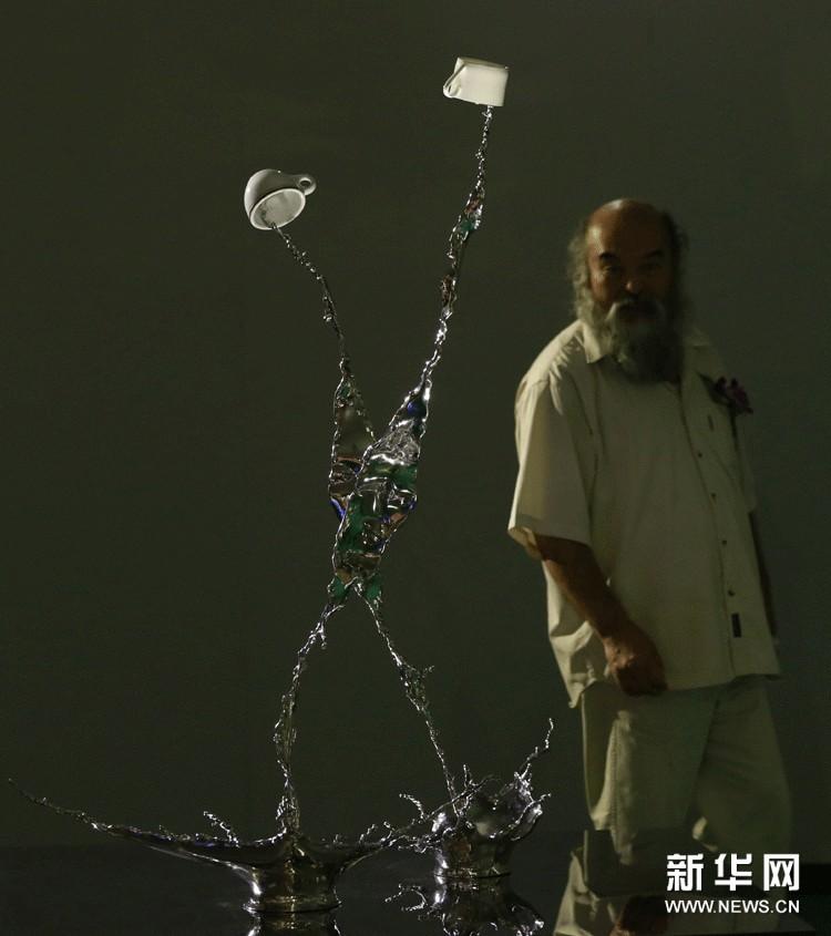 """观众在展厅内欣赏香港艺术家曾章成的不锈钢雕塑作品《鸳鸯》。该作品以两杯香港茶餐厅地道饮品""""鸳鸯""""在空中流淌、交融,寓意香港中西合璧的文化特色。"""