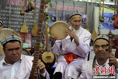 图为博览会现场一支民族乐队正在演奏,其间一位打手鼓的老人陶醉在音乐中。刘新 摄
