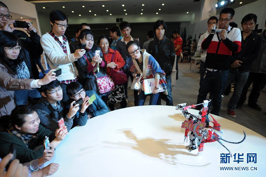 """11月1日,参观者被一个穿着京剧服装的仿人机器人的表演所吸引。当日,由中国人工智能学会和杭州市政府主办的以""""智能体验智慧生活""""为主题的2012第二届中国智能博览会在浙江世贸国际展览中心开幕。新华社记者 鞠焕宗 摄"""