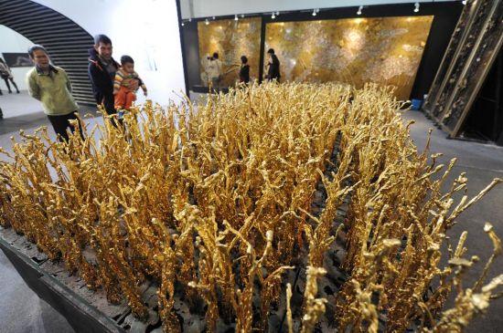 11月8日,观众在参观展出的熔铜艺术作品《金稻》。