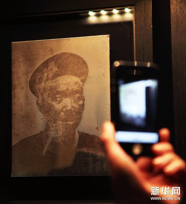 """11月13日,在法国巴黎中国文化中心举办的""""前尘影视——最早的中国照片展""""上,参观者欣赏埃迪尔拍摄的照片。"""