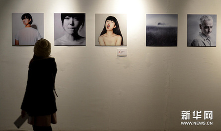12月25日,参观者在第五届中国美术学院平面设计艺术节上欣赏摄影设计类作品。新华网图片 施健学 摄