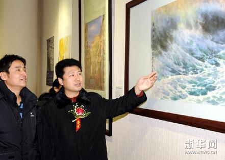 12月30日,画家李冬(右)在向观众介绍自己的画作。新华网图片 唐召明 摄