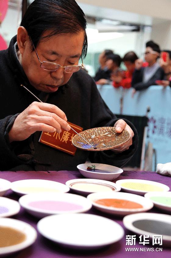 1月22日,中国工艺美术大师、国家非物质文化遗产传承人张同禄在展览开幕式现场为观众示范景泰蓝制作工艺。