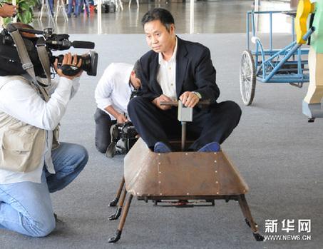 2月4日,在巴西城市巴西利亚举行的《农民达芬奇》展览上,来自北京通州区的农民发明家吴玉禄向媒体演示自己制造的机器人。新华网图片 刘彤 摄