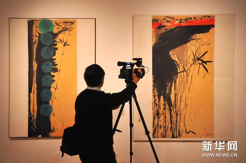 """2月22日,在美国旧金山州立大学举行的""""水墨时刻""""联展媒体预展上,一名记者拍摄参展作品。"""