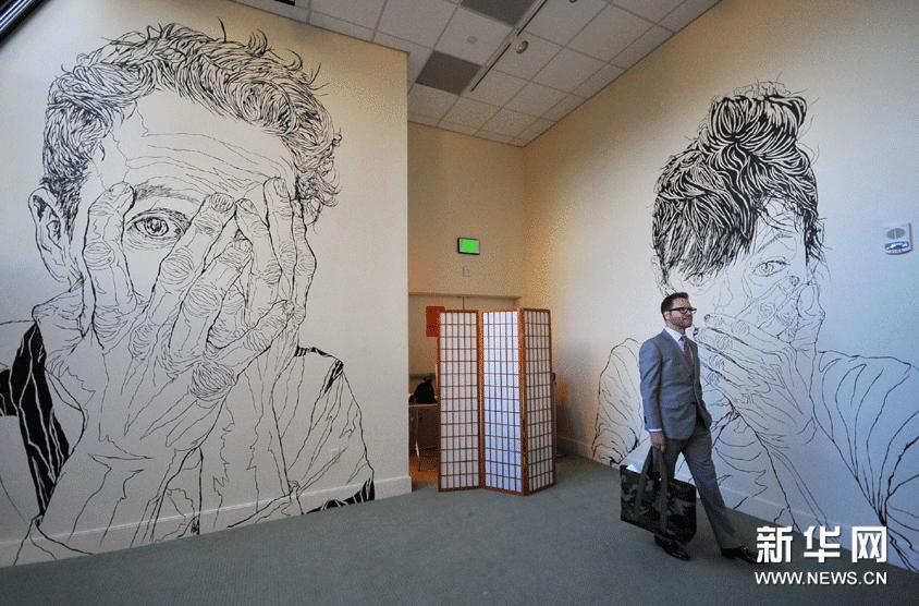 """2月22日,在美国旧金山中华文化中心举行的""""水墨时刻""""联展媒体预展上,一名记者欣赏美国画家乔纳森•沃尔雷文的巨幅线描人像。"""