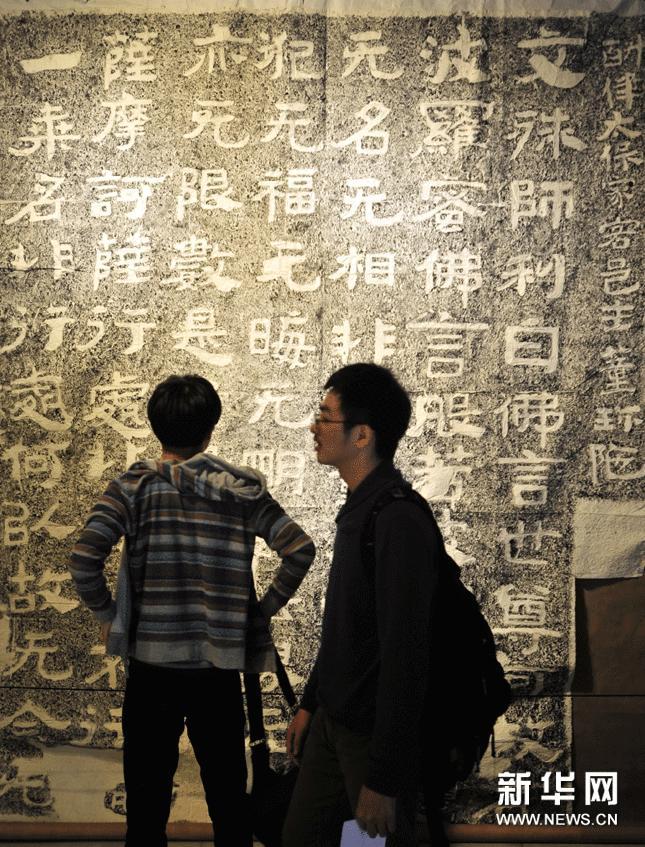 2月25日,观众在台北举办的山东佛教刻经拓片展上欣赏峄山妖精洞经文拓片。