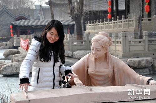 """2月23日,在榆次老城新春蜡像展上,一名游客在模仿""""蜡人""""的弹琴动作。新华网图片 王飞航 摄"""