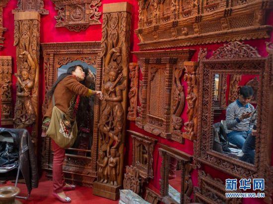 2月28日,参观者在展会上欣赏来自尼泊尔的木制品。
