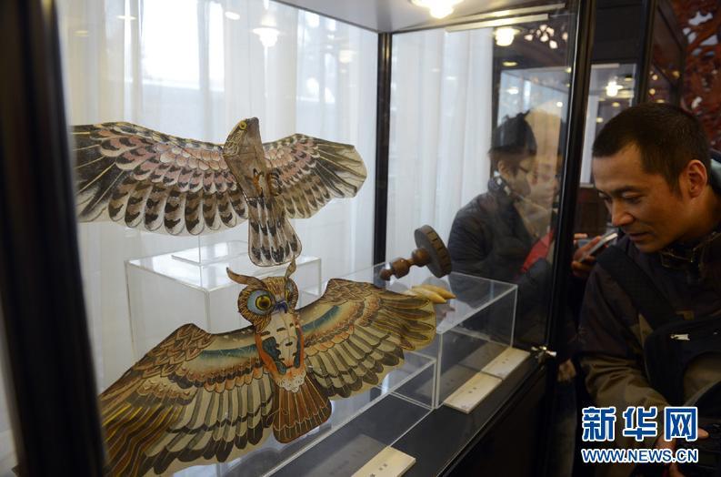 4月4日,游客在展览上观看民国时期的用于娱乐的猫头鹰风筝。