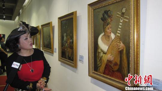 图为欧洲中国艺术院院长张蝶,向大家介绍勒迈先生创作的自己弹琵琶画像。 刘家宇 摄