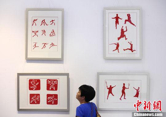 7月3日,观众被展出的以体育为题材的剪纸作品吸引。中新社发 泱波 摄