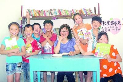 郁雪群老师(中)与阅读点儿童在一起。光明日报通讯员 范雪强摄