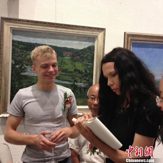 图为俄罗斯美女画家在为油画爱好者签名。 孙权 摄