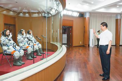 6月11日,中共中央总书记、国家主席、中央军委主席习近平在酒泉卫星发射中心观看神舟十号载人飞船发射。这是习近平向即将出征的航天员聂海胜、张晓光、王亚平挥手致意。新华社记者李学仁摄