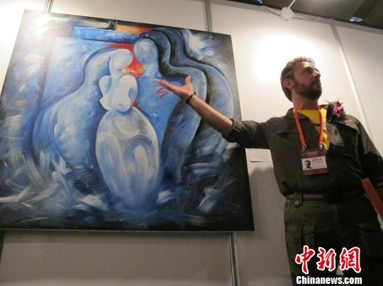 马哈茂德•塔拉尔向记者介绍他创作的画作。 杨喆 摄
