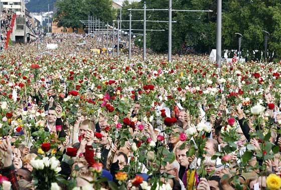 """2011年7月25日,15万多挪威民众手持红白玫瑰悼念""""7·22""""爆炸枪击案遇难者。(美联社) 近年来,尽管种族主义在欧洲有所抬头,甚至在挪威发生了骇人听闻的""""7·22""""爆炸枪击案,造成包括儿童在内的77人遇难,但该国表现出了深沉的宽容:玫瑰成了这种宽容的象征,挪威政府当时降低进口玫瑰的关税,方便所有人悼念死者。在这一罕见的事件中,杀手布雷维克被判21年监禁,但惩罚仅局限于他本人。(来源:大西洋月刊作者:多兰·拉尔"""