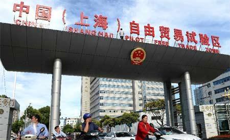"""9月26日,人们从上海外高桥保税区三号门的""""中国(上海)自由贸易试验区""""字牌下经过。"""