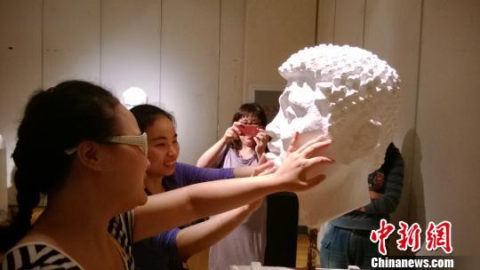 视障孩子在用手感受雕塑。 张骏 摄