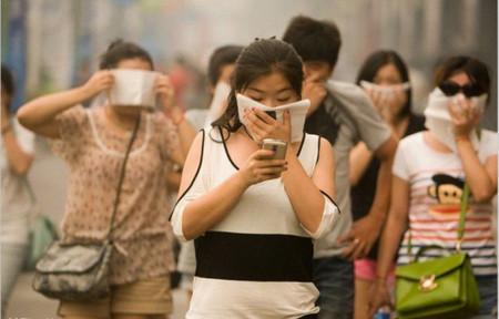 因为雾霾,行人不得不采取防护措施。