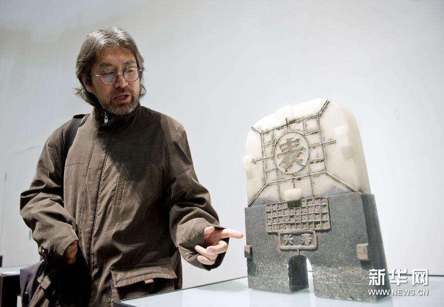 (6)1月13日,在杭州中国美术学院美术馆,中国艺术家关东海在讲解他创作的玻璃艺术作品《城门·表》。